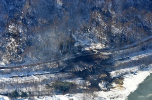 This aerial view of the derailed cars, from a CSX train carrying Bakken crude oil, near Adena Village, W. Va., show limited road access for first responders (near the middle of the frame) and the proximity of the Kanawha River (at the bottom of the frame). Photo information at bottom of post.
